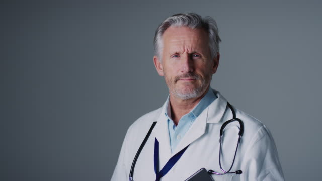 studio porträtt av mogen manlig läkare med digital tablett bär vit kappa mot grå bakgrund - hospital studio bildbanksvideor och videomaterial från bakom kulisserna