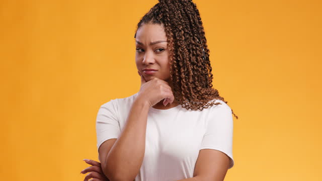 Studio portrait of young doubtful woman looking at camera with suspicion and doubt, orange studio background