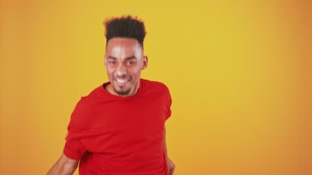 studio shot of excited african american guy dancing fastly, orange studio background - flirtować filmów i materiałów b-roll