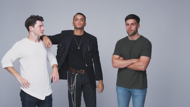 stockvideo's en b-roll-footage met studio shot van jonge onafhankelijke multi-culturele mannelijke vrienden op zoek naar de camera in slow motion - drie personen