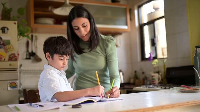 studerar hemma. - enbarnsfamilj bildbanksvideor och videomaterial från bakom kulisserna
