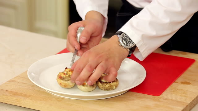 Stuffed champignon on white plate with salad Chef is serving a plate of stuffed champignon with salad stuffed stock videos & royalty-free footage