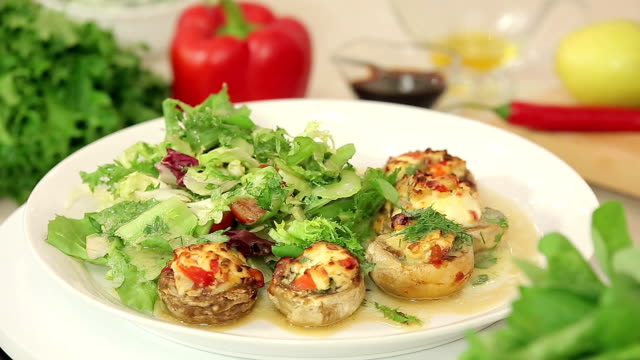 Stuffed champignon on white plate with salad Stuffed champignon on white plate with salad, meal presentation stuffed stock videos & royalty-free footage