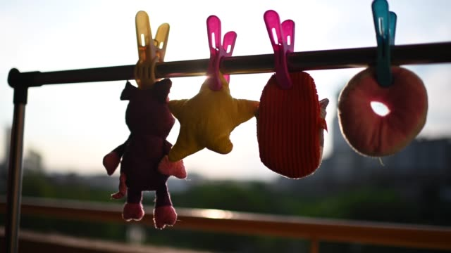 stuffed soft Toy clothesline clothespin hanging at balcony in the morning