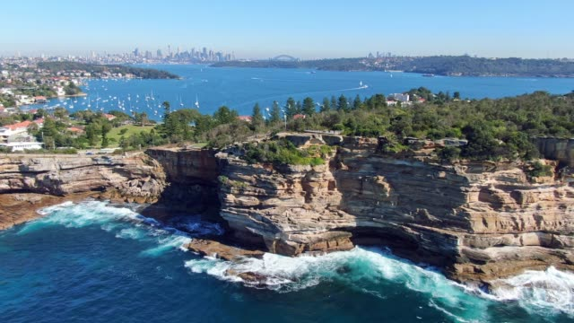 Stunning 4k panoramic aerial drone flight of the Gap, an ocean cliff on the South Head peninsula in the suburb of Watson's Bay in eastern Sydney. The central business district of Sydney in background.