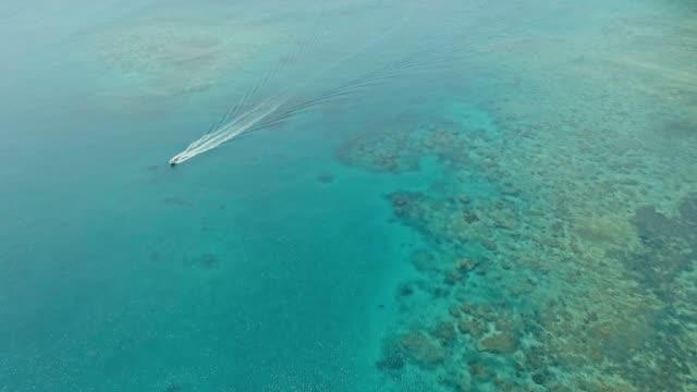 vídeos y material grabado en eventos de stock de impresionante imagen aérea drone de un un barco de pesca pequeño entrando en una un anclaje de océano mar un canal situado al lado de un arrecife de coral en aguas cristalinas de azul azul en una remota isla tropical aislada - micronesia
