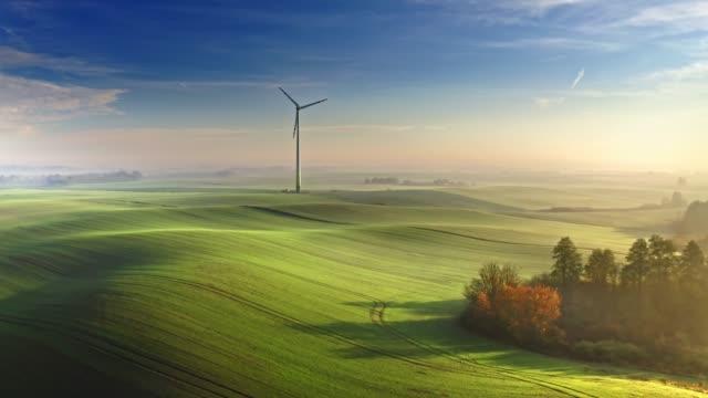 vídeos y material grabado en eventos de stock de impresionante aerogenerador brumoso en campo verde al amanecer - polonia