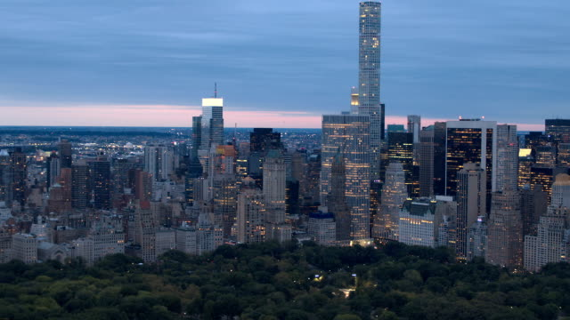 AERIAL: Stunning Midtown Manhattan and Central Park sklyine at pink light dawn AERIAL HELI SHOT: Lights shining in windows of giant glassy skyscrapers, office buildings and luxury condomoniums overlooking lush green Central park on tranquil early morning, New York City Manhattan central park manhattan stock videos & royalty-free footage