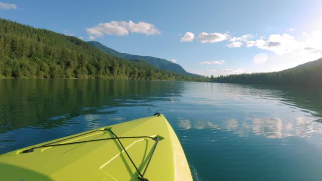 ターコイズブルーの水に黄色のカヤックボートの前面で見事な平和な湖ショット ビデオ
