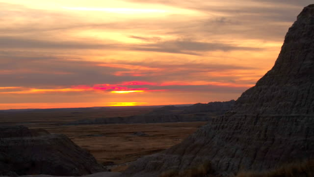 AERIAL: Stunning rocky sandstone mountains rising above dry prairie at Badlands video