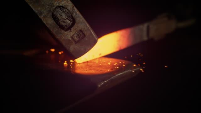 slow motion: incredibile colpo di pezzo di metallo caldo tenuto dalle pinng e colpito da martello - fabbro ferraio video stock e b–roll