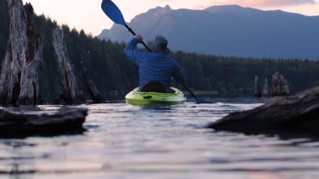 男の手漕ぎボートスローモーションで山の湖に見事なサンセットカヤックエスケープ ビデオ