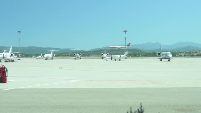 Stunning view of some private jets parked on a parking lot in the Sardinian airport while a commercial airplane is landing. Sardinia, Italy.