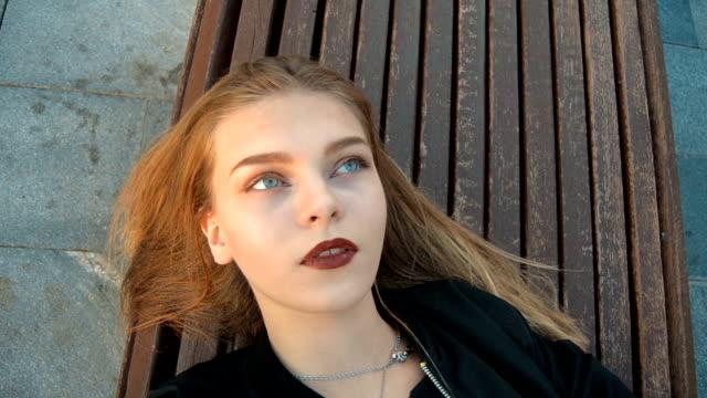 見事な金髪の若いは屋外のベンチで休憩します。 - ベンチ点の映像素材/bロール