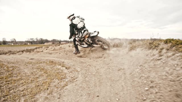 slo mo stunt dirt biker drifting through the turn - motocross video stock e b–roll