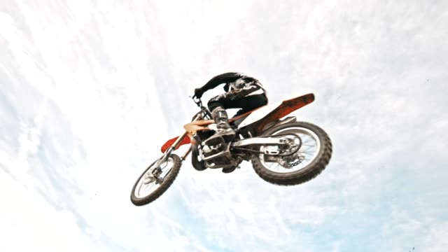 slo mo stunt dirt biker jumping over the camera - motocross video stock e b–roll