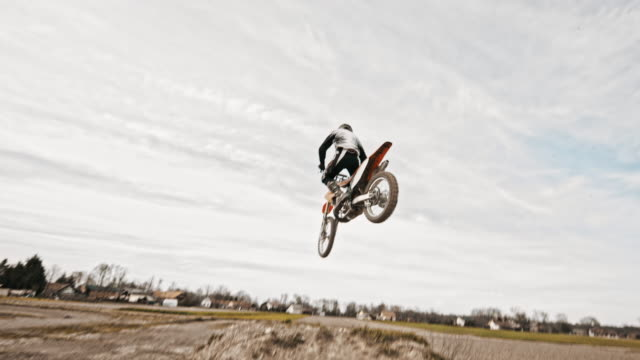 stunt dirt biker jumping over the camera - motocross video stock e b–roll