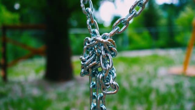 下にぶら下がっている頑丈なスチール チェーンはシングル ノットで接続されます。夏の公園で子供の魅力は金属製のマウント - 鎖の輪点の映像素材/bロール