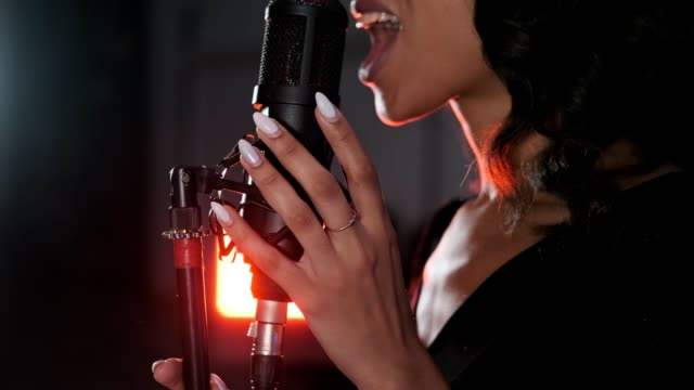 Stylish african-american woman singing in studio. Close-up of brunette woman