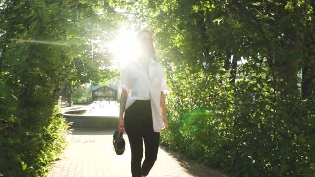 スタイリッシュで自信を持って若い女性スローモーションで日当たりの良い公園を歩いて - スーパーモデル点の映像素材/bロール