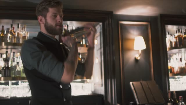 Stylish bearded barman making cocktail with shaker video