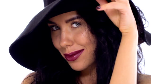 vidéos et rushes de élégant brunette caucasien au soleil-chapeau à fond blanc - rouge à lèvres rouge