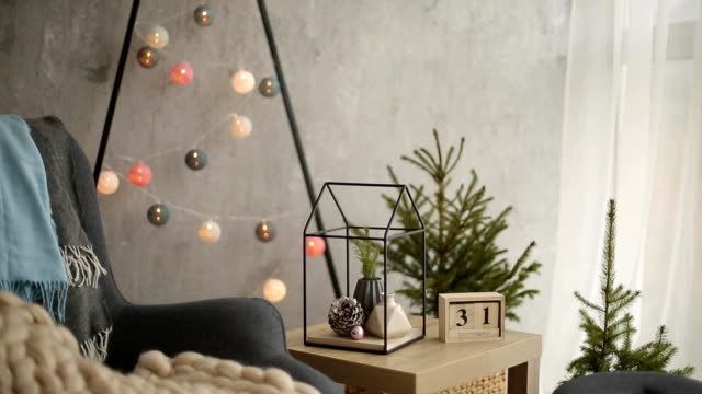 stylish christmas scandinavian interior with an elegant armchair and warm merinos plaid. comfort home with nordic new year decor. minimalistic christmas tree with garlands and lights in light room - arredamento video stock e b–roll
