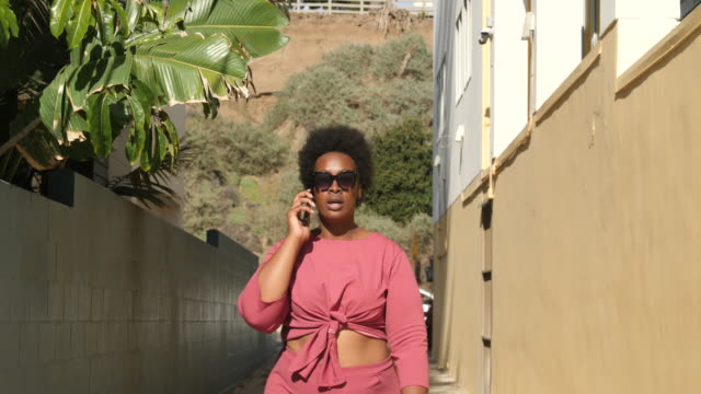 stylish curvy woman talking on cell phone outdoors - body positive video stock e b–roll