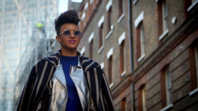 stylish fashion blogger walking along urban street - london fashion stock videos and b-roll footage