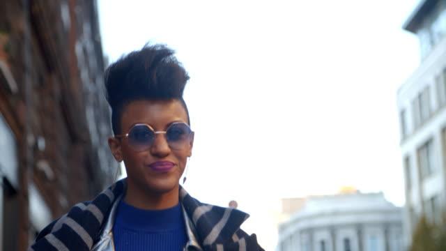 都市通りに沿って歩いてスタイリッシュなファッションのブロガー ビデオ