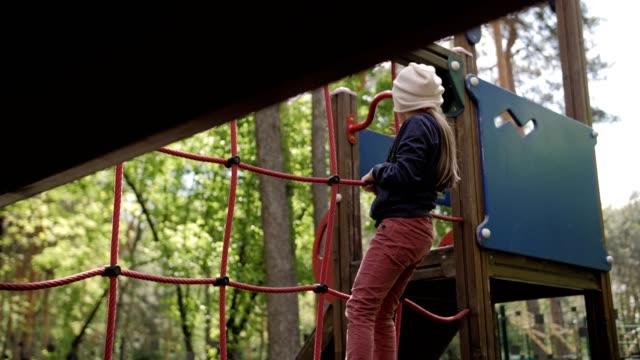 4k slow motion stilvolle mädchen spielen auf dem spielplatz im park - kopfbedeckung stock-videos und b-roll-filmmaterial