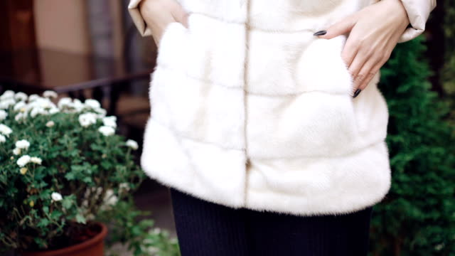 Stylish girl posing to camera in fur coat on the street FullHD video