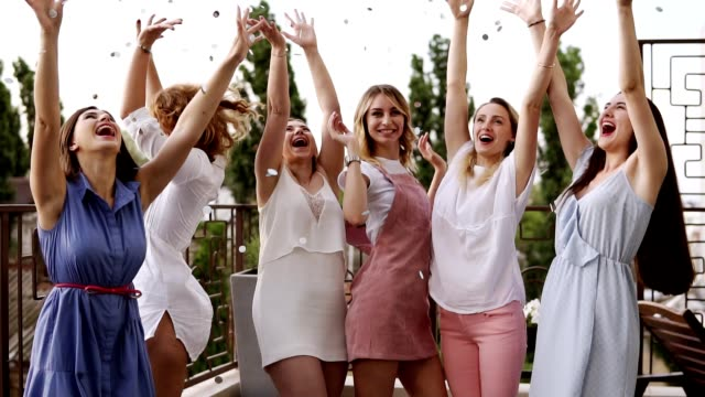 stylish girls on bachelorette party outside on the terrace. throw silver confetti into the air. happy lifestyle, enjoy life. dancing and laughing. daytime. slow motion - bachelorette party stock videos and b-roll footage