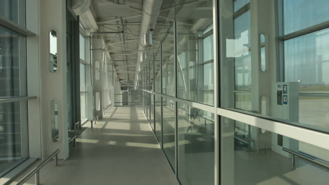Stylish glass corridor in airport terminal to runway with planes.