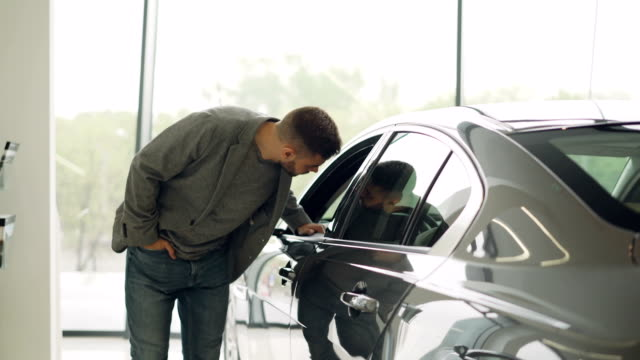 vídeos de stock e filmes b-roll de stylish guy is choosing new automobile walking around luxury car and touching it in car dealership. rich people, transportation and business class vehicles concept. - new