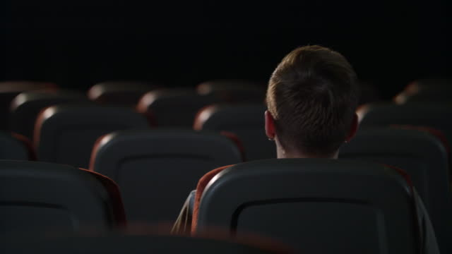 Stylish guy sitting in empty movie theater alone. Back view of man in cinema Stylish guy sitting in empty movie theater alone. Back view of man head in cinema. Lonely guy sitting in empty room after movie. Young man sitting alone in empty cinema lounge chair stock videos & royalty-free footage