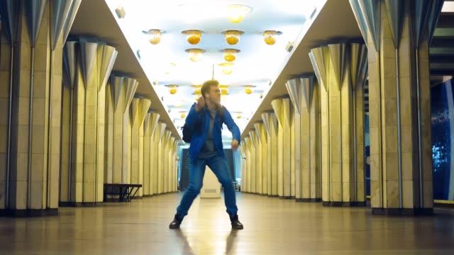 vidéos et rushes de guy élégant avec des lunettes dansant élégamment et agitant ses bras dans le métro. le jeune homme écoute la musique avec des écouteurs et saute à la station. - homme faire coucou voiture