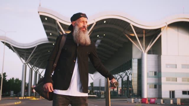 vídeos y material grabado en eventos de stock de hombre de mediana edad guapo elegante con pie y barba larga gris con longboard durante la puesta de sol sobre fondo urbano - moda hipster