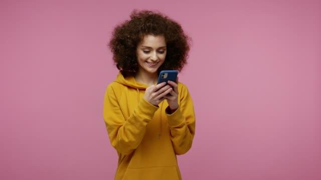 stilvolle glückliche mädchen afro frisur in hoodie-typisierung nachricht auf handy und lächelnd, chatten - farbiger hintergrund stock-videos und b-roll-filmmaterial