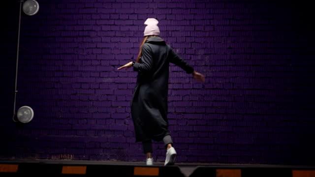 vídeos de stock, filmes e b-roll de uma garota à moda hipster em copos elegantes e uma dança de chapéu perto uma violeta de tijolo da parede em fones de ouvido. mo lento - moda hipster