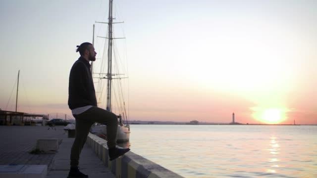 stockvideo's en b-roll-footage met man van de stijlvolle hipster op zee haven achtergrond tijdens zonsondergang, die opzij - street style