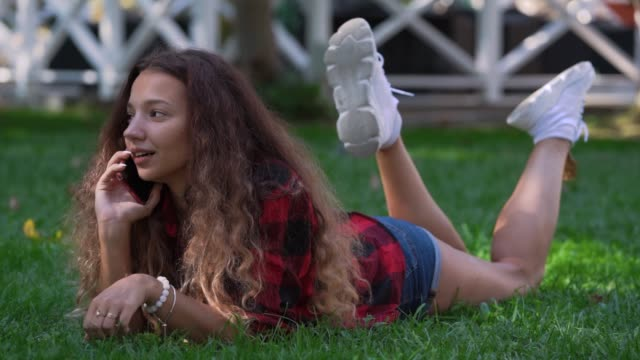 Stylish lady with curly hair lies on grass talking on phone