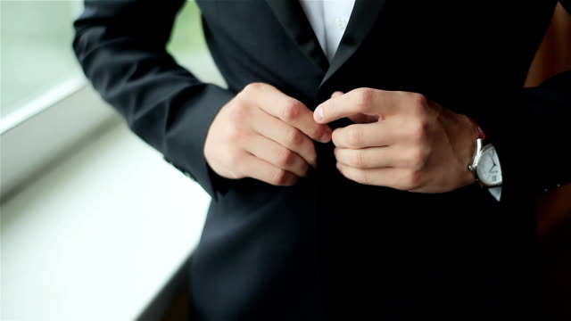 Stylish man dressed in suit buttoning jacket close up. Male hands of confident gentleman adjust outfit preparing for formal evening. Image establishment leadership lifestyle masculinity style success video