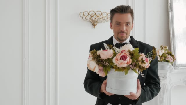 Stylish man holds out a bouquet