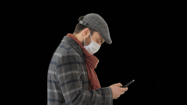 Stylish man in medical mask walking and using smart phone, Alpha Channel