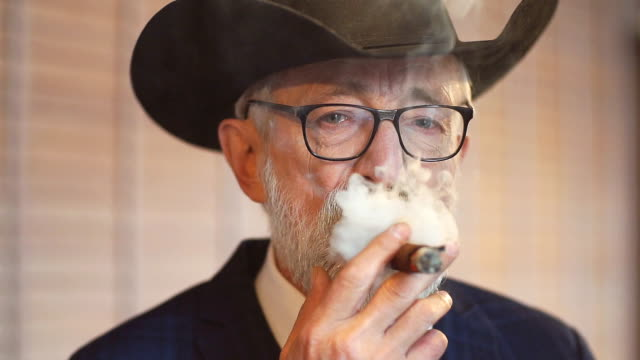 Stylish old man in wide brimmed hat and rich blue mens suit smoking cigar indoor