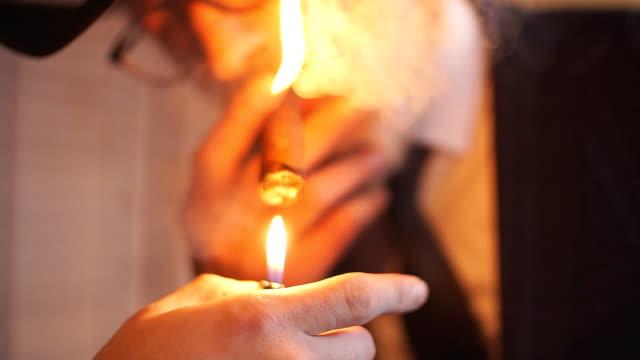 geniş kapalı şapka sigara puro iç şık yaşlı adam - puro stok videoları ve detay görüntü çekimi