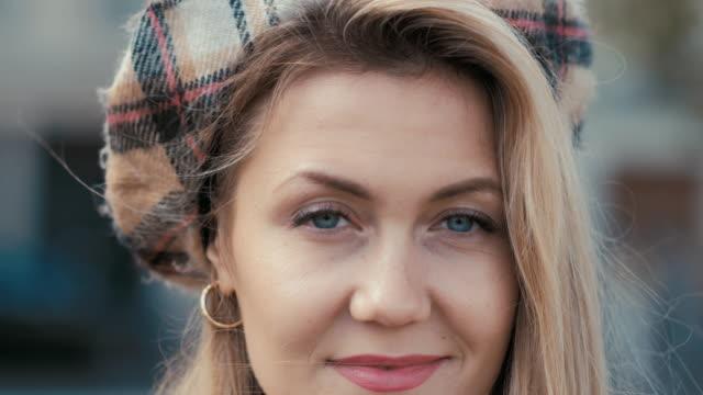 vídeos y material grabado en eventos de stock de elegante mujer de negocios parisina con una boina y una gabardina beige sonrisas eróticamente en la cámara y se aleja - moda parisina