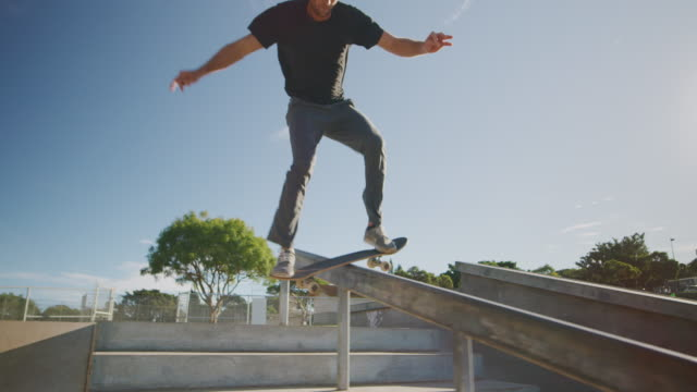 Stylish skateboarder grinding on a rail Extreme skateboarder doing a backside grind on a handrail down stairs in a skatepark in the morning, skateboarding tricks in slow motion skateboarding stock videos & royalty-free footage