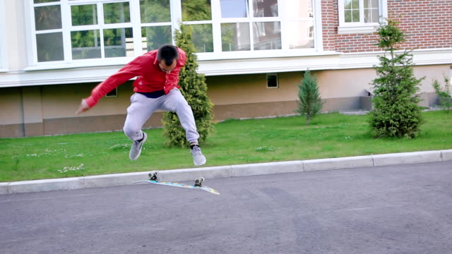 Stylish skateboarder in red coat performing cool jump on his skateboard video